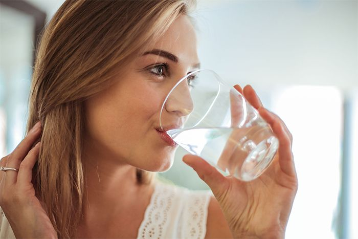 femme belle peau buvant un verre eau